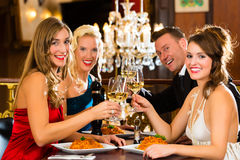 Friends in a very good restaurant clink glasses Stock Photography