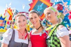 Friends visiting Bavarian fair having fun at carousel stock photo