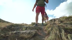 Friends walking along hiking trail path. Group of friends people summer adventure journey in mountain nature outdoors.