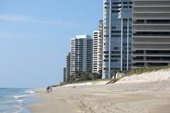 Friends walking along Singer Island beach front condos Royalty Free Stock Image