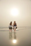Friends walking on beautiful foggy beach at sunrise. Stock Photography