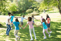 Friends walking in a circle at park. Group of multiethnic friends walking in a circle at park stock photo