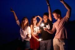 Friends walking, dancing and having fun during night party at the seaside with bengal sparkler lights in their hands. Young teenagers partying on the beach stock photography