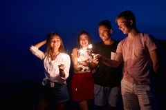 Friends walking, dancing and having fun during night party at the seaside with bengal sparkler lights in their hands. Young teenagers partying on the beach royalty free stock photography