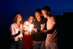 Friends walking, dancing and having fun during night party at the seaside with bengal sparkler lights in their hands. Young teenagers partying on the beach royalty free stock photos