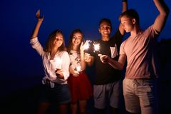 Friends walking, dancing and having fun during night party at the seaside with bengal sparkler lights in their hands. Young teenagers partying on the beach stock images