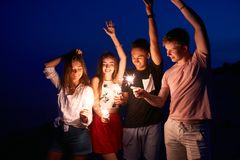 Friends walking, dancing and having fun during night party at the seaside with bengal sparkler lights in their hands. Young teenagers partying on the beach royalty free stock image