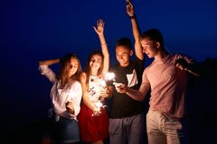 Friends walking, dancing and having fun during night party at the seaside with bengal sparkler lights in their hands. Young teenagers partying on the beach stock photo