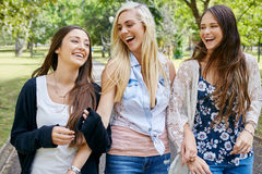 Friends walking fun. Happy fun teen girl friends walking in park laughing on weekend royalty free stock photography