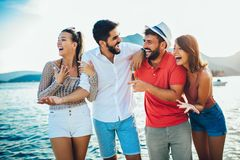 Friends walking by the harbor of a touristic sea resort stock image