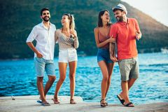 Friends walking by the harbor of a touristic sea resort stock images