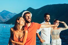 Friends walking by the harbor of a touristic sea resort stock photography