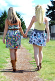 Friends Walking and Holding Hands. Two beautiful young blond ladies in a dress and skirt walk down a dirt pathway on a bright summer's day while holding hands stock photography