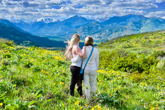 Friends walking on meadows in North Cascades National Park. Arnica blooming in Cascade Mountains. Winthrop. Washington. The United States Royalty Free Stock Photography