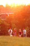 Friends walking in park at sunset. stock photos