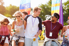 Friends walking together through a music festival site Royalty Free Stock Images