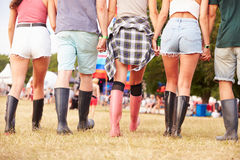Friends walking together at a music festival site, back view Royalty Free Stock Image