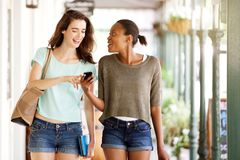 Friends walking together using mobile phone Royalty Free Stock Photos