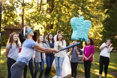 Friends watch teenage girl hitting a pi�ata on her birthday royalty free stock images