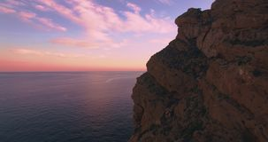Friends watching beautiful sunset over ocean cliff. Aerial shot from drone flying toward sunset sun in ocean next to mountain cliff edge with two small girls stock video