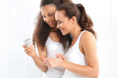 Friends watching cosmetics, cream, lotion. Stock Photos