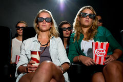 Friends watching 3D movie at cinema Stock Images