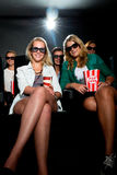 Friends watching 3D movie at cinema stock photo