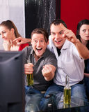 Friends watching exciting game at TV. Two couples watching sports in the telly, the guys are really excited, drink beer and cheer their team while the girls are Stock Photos