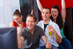 Friends watching exciting game at TV. Two couples watching sports in the telly, they all are really excited, drink beer and cheer their team Stock Images