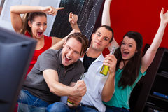 Friends watching exciting game at TV. Two couples watching sports in the telly, they all are really excited, drink beer and cheer their team Royalty Free Stock Images