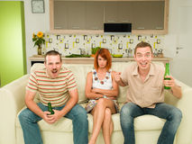 Friends watching an exciting game. Two men sitting on couch watching television, in kitchen, holding beers and screaming, with an upset women between them Royalty Free Stock Photos
