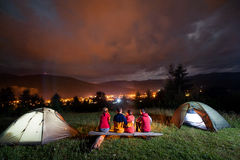 Friends watching fire together beside camp and tents. Friends sitting on a bench made of logs and watching fire together beside camp and tents in night on the Stock Photography