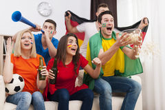 Friends watching football game on TV Stock Images