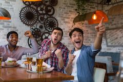 Friends watching football game on TV and drinking beer stock photos