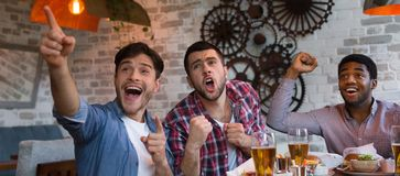 Friends watching football game on TV and drinking beer royalty free stock images