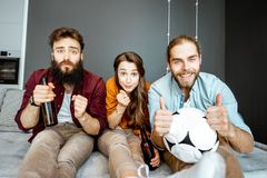 Friends watching football match at home royalty free stock photography