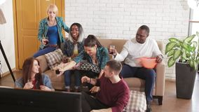 Friends watching football match on TV stock footage