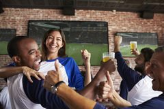 Friends Watching Game In Sports Bar On Screens Celebrating Stock Photography