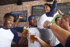 Friends Watching Game In Sports Bar On Screens Celebrating Royalty Free Stock Photography