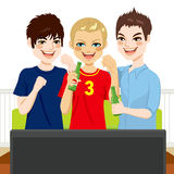Friends Watching Game. Three young friends watching sports game on television together Stock Photography