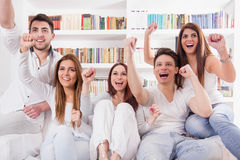 Friends watching game on tv cheering Stock Photography
