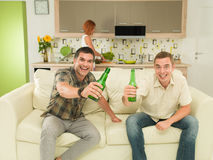 Friends watching a game. Two excited men sitting on couch watching television, in kitchen, holding beers and screaming, with a women in background cooking Royalty Free Stock Photo