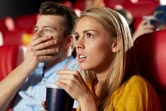 Friends watching horror movie in theater. Cinema, entertainment and people concept - couple drinking soda and watching horror, drama or thriller movie in theater Stock Photo