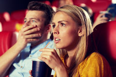 Friends watching horror movie in theater. Cinema, entertainment and people concept - couple drinking soda and watching horror, drama or thriller movie in theater Stock Images