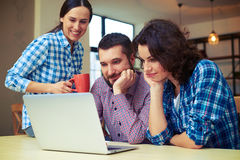 Friends watching interesting video on laptop Stock Photography
