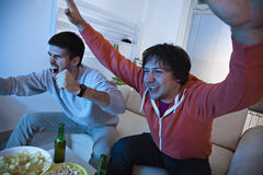 Friends Watching Match On TV Stock Photography