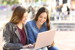 Friends watching media on line with a laptop. Two friends watching media content on line together with a laptop sitting in a bench in the street with an urban Stock Image