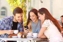 Friends watching media in a smart phone in a coffee shop. Three happy friends watching social media in a smart phone in a coffee shop Stock Images