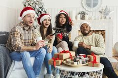 Friends watching movie and having fun at Christmas eve. Traditional Christmas movie. Excited multiethnic friends watching TV at home, spending holiday time stock images