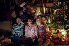 Friends watching movie on laptop on Christmas eve. Happy friends watching movie on laptop on Christmas eve royalty free stock image